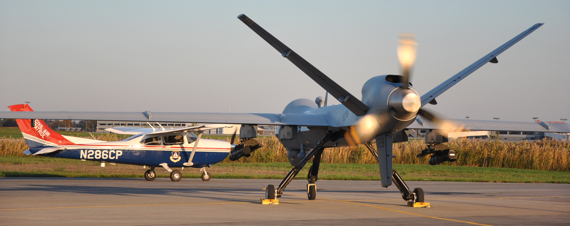 Civil Air Patrol aircraft taxis past USAF Reaper on runway