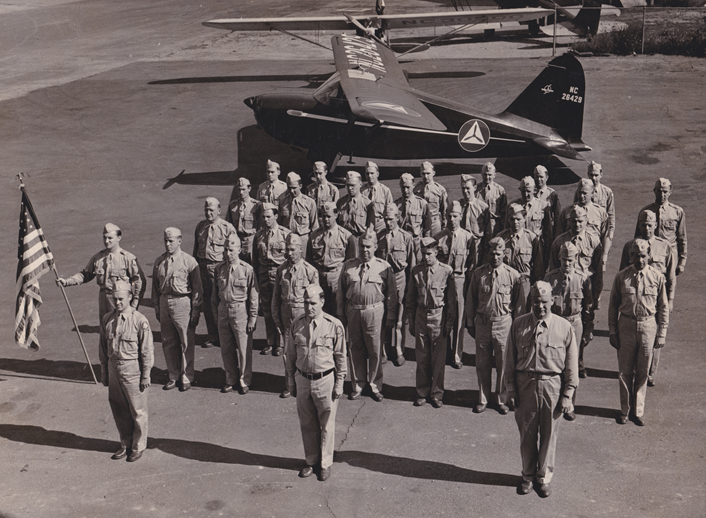 World War 2 Civil Air Patrol members in formation in front of airplane